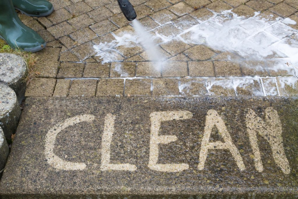 Cleaning a sidewalk with a homemade power washer detergent made specifically for sidewalks
